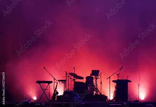 concert stage on rock festival, music instruments silhouettes, colorful background with copy space - 312736429