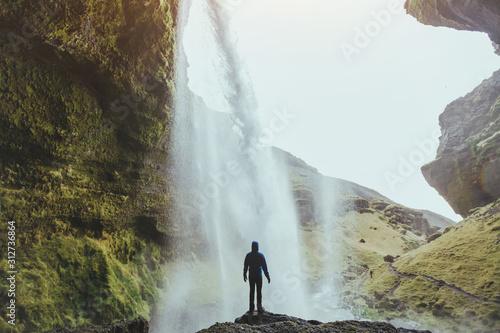 Obraz outdoor adventure, person standing near waterfall Kvernufoss in Iceland, nature landscape - fototapety do salonu