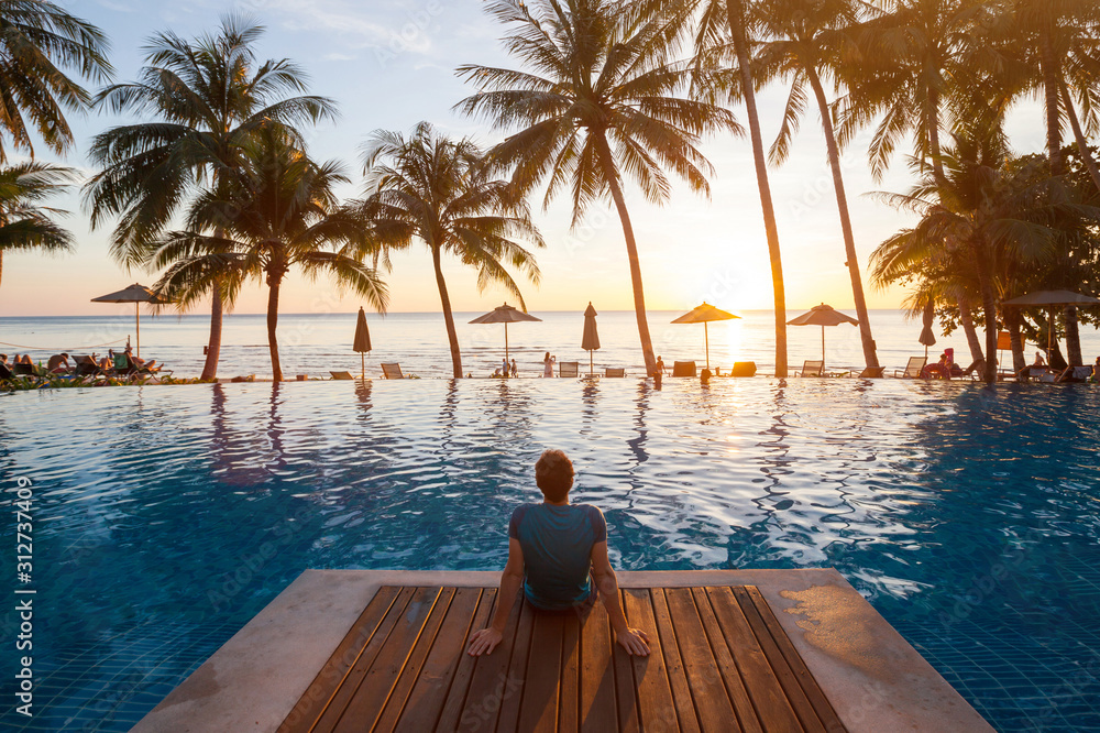 Fototapeta summer holiday getaway in luxury beach hotel, tourist relaxing near luxurious swimming pool at sunset, vacation on tropical island