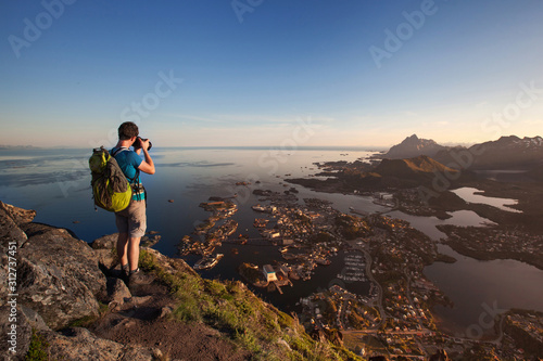 Photo tourist in Svolvaer taking photo of Lofoten, hiking in Norway, tourism with back