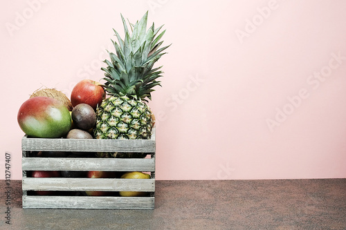 Fresh fruits in vintage box on pink background