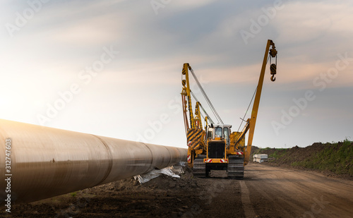 Fototapeta Crane digging a channel for gas pipeline obraz