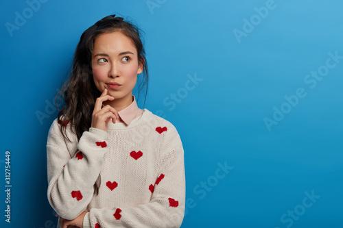 Fotografie, Obraz Contemplative pretty millennial young Asian woman looks away, builds plans in mi