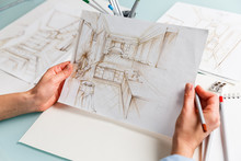Interior Designer Holding  Pencil Sketch Of A Kitchen In A Process Of Drawing.