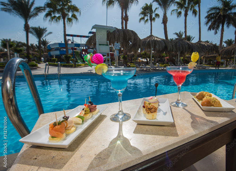 Fototapeta Cocktail drinks on table by a swimming pool of luxury hotel resort