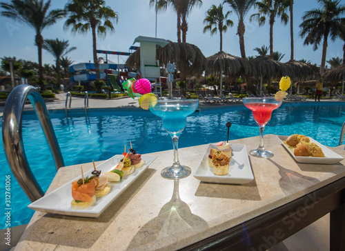 Fototapeta Cocktail drinks on table by a swimming pool of luxury hotel resort obraz