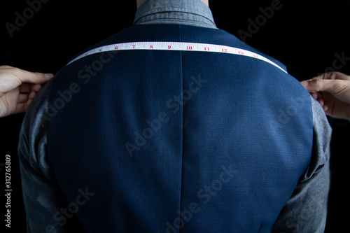 The dressmaker was measuring the width of the back of the man wearing a blue suit on black background Slika na platnu