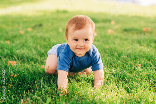 Obraz Adorable red haired baby boy crawling on fresh green grass in summer park - fototapety do salonu