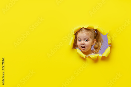 Photo Little surprised child looking, peeping through the bright yellow paper hole
