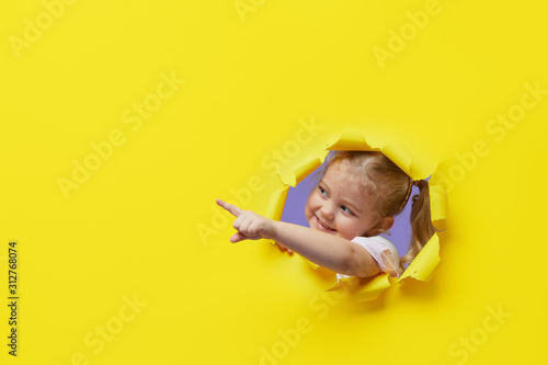 Fototapeta Little surprised child looking, peeping through the bright yellow paper hole. Showing hand to side. Advertise childrens goods. Copy space for text. obraz
