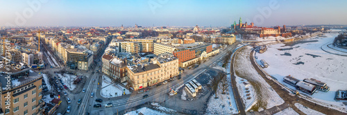 Fototapeta Krakow, Poland. Wide winter aerial panorama with old city, Wawel cathedral and castle, partly frozen Vistula river, harbor, ships, promenades by the riverside, cars, parking and streets. Sunset light obraz