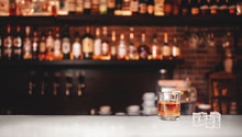Glass Of Whiskey With Ice Stands On Bar Counter, Dark Brown Background