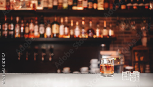 Foto Glass of whiskey with ice stands on bar counter, dark brown background