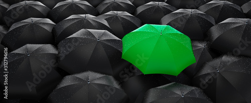 Green umbrella stand out from the crowd of many black umbrellas - being different concept