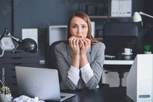 Worried young woman in office