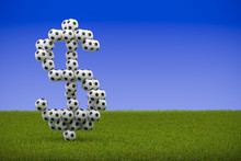 3D Render: Classic Black And White Soccer Balls Forming A Dollar Sign On Grass And Blue Sky Background. Big Business / Corruption In Sports, Football, Soccer. Copy Space To The Right