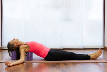 Slim Woman Rests Back And Head On Blocks At Yoga Studio. Female Yogi On Pink Tank Top And Black Pants Lying On Mat. Healthy Lifestyle, Exercise Concepts