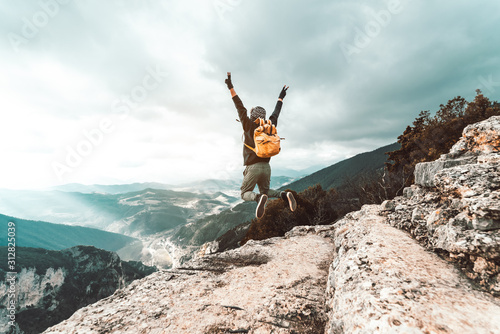 Obraz Young man traveler jumps on a background of mountain raising arms to the sky - fototapety do salonu
