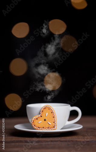Cup of coffee and cookies on a table with fairy lights
