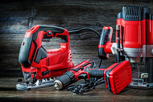 Electric Hand Tools Red Corded Jigsaw Cordless Drill And Small Plunge Router Milling Machine Portable Mini Wood Router On Vintage Wooden Background