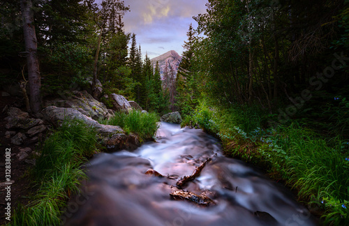 Fototapeta Long exposure of a river in the Rocky Mountains at sunset. There are pine trees lining the river and a mountain peak can be seen in the distance. obraz