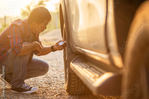 Fototapeta Asian man checking air pressure and filling air in the tires of his car obraz