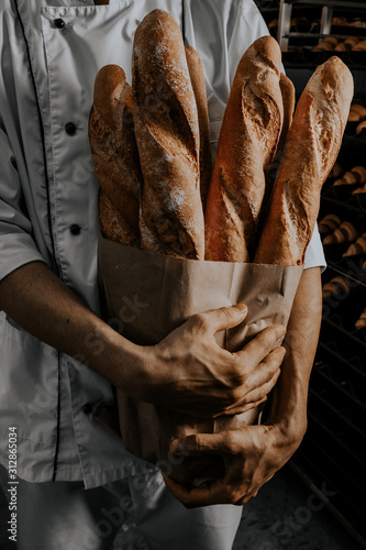 Photo baker's hands are holding a craft baguette with baguettes on a dark background
