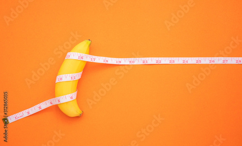 Yellow banana with measurement tape on orange background Fotobehang