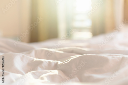 Obraz White bedding sheets and pillow in hotel room at morning time with sunlight from windows - fototapety do salonu