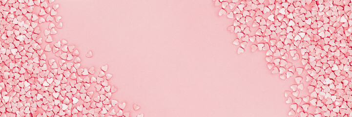 Trendy shining silver candy pink hearts background of cake sprinkles in flat lay with copy space, for feminine blogger or festive love and Valentine's Day concept. Long banner mockup