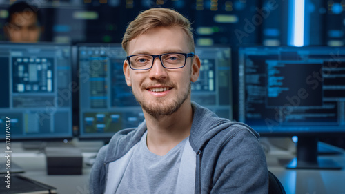 Fotografie, Tablou Portrait of a Smart and Handsome IT Specialist Wearing Glasses Smiles, Behind Hi