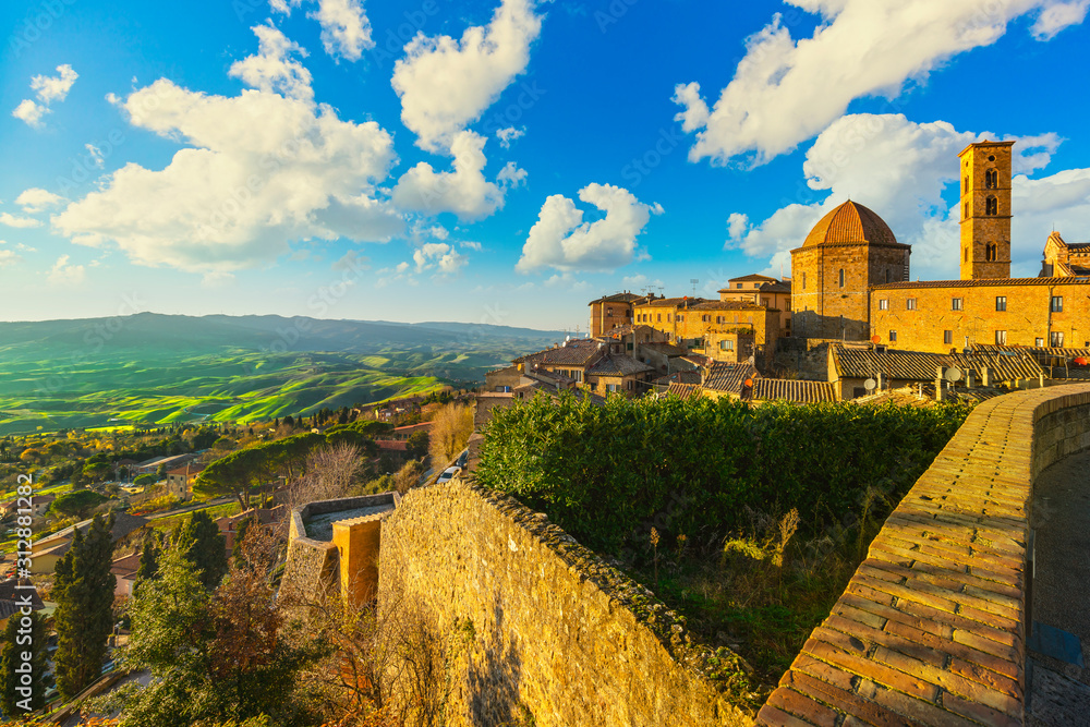 Fototapeta Tuscany, Volterra town skyline, church and panorama view on sunset. Italy