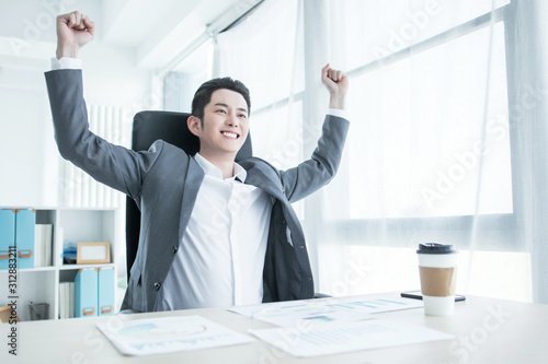 Portrait of excited Asian man holding hands folded in elbows and screaming in joy against white background Tableau sur Toile