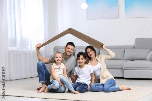 Fototapeta Happy family sitting under cardboard roof at home. Insurance concept obraz