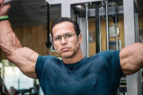 Fototapeta Detail of the face of a man doing strength with glasses doing bodybuilding exercises obraz na płótnie