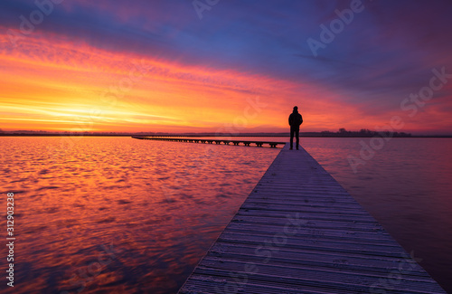 Obraz na plátně A man enjoying the colorful  dawn on a jetty in a lake