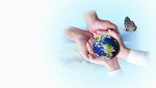 Two Pairs Of Hands Helping To Support The Globe With Butterflies On A Blue And White Background. Safe World And Ecology Concept. Elements Of This Image Furnished By NASA