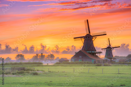 Fotomural Traditional village with dutch windmills and river at sunset, Holland, Netherlands