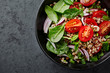 Buckwheat salad with cherry tomatoes, spinach, spring onion and mint leaves. Copy space. Dark stone background