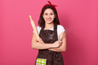 canvas print picture - Horizontal shot of confident cheerful beautiful young woman posing isolated over pink background in studio, having folded arms, holding rolling pin and whisk in both hands. Culinary concept.