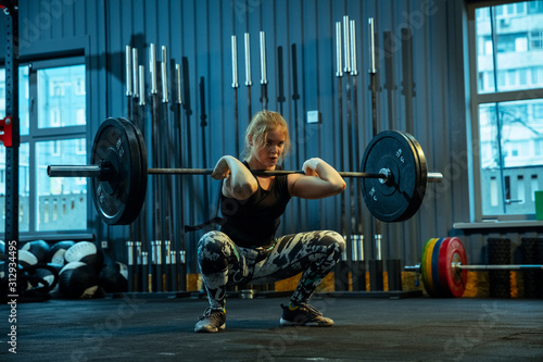 Fotografiet  Caucasian teenage girl practicing in weightlifting in gym