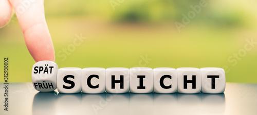 Fotografie, Obraz Hand dreht einen Würfel und ändert das Wort Frühschicht in Spätschicht, oder umgekehrt