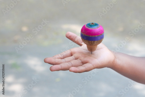 Fotografia Classic wooden spinning top toy over the palm