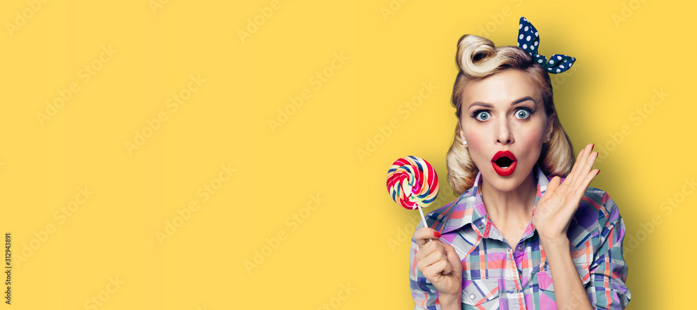 Fototapeta Excited surprised woman with candy lollipop. Girl pin up, gesturing. Retro fashion and vintage concept. Yellow color background. Copy space for some advertise slogan or text.