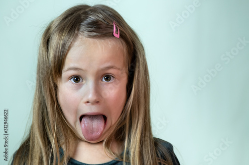 Obraz Close-up portrait of little girl with long hair sticking out her tongue. - fototapety do salonu
