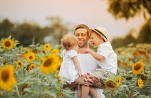 A Happy Family Walks In A Field Of Sunflowers. Young Handsome Dad With Two Children In A Sunflower Field.