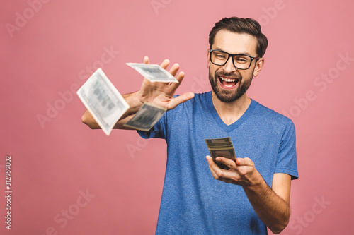 Fototapeta Portrait of a happy young businessman throwing out money banknotes isolated over pink background. obraz