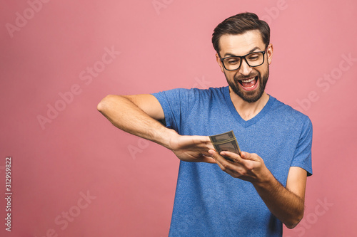 Fotografía  Portrait of a happy young businessman throwing out money banknotes isolated over pink background