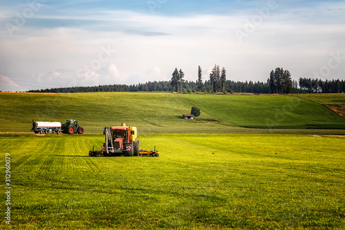 Slika na platnu Application of manure on arable farmland with the heavy tractor who works at the