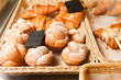 Delicious freshly baked pastries in a pastry shop. Many buns and croissants on a shelf of a baking shop